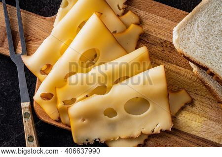 Sliced smoked hard cheese on cutting board. Top view.