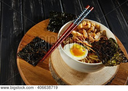 Japanese Ramen Soup With Chicken, Egg, Garlic And Noodles On A Dark Wooden Background. Asian Miso Ra