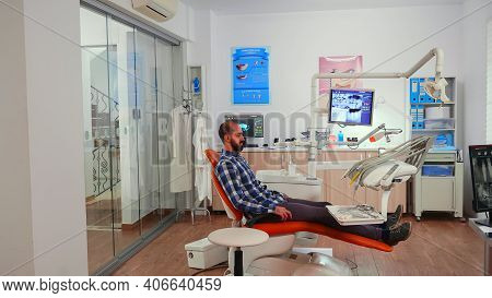 Nurse Inviting Next Patient In Stomatology Room Showing To Lie On Chair. Dentistry Assistant Sitting