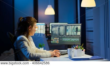 Videographer Working At Computer From Business Office, Editing Video And Audio Footage At Night. Con
