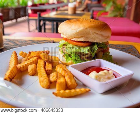 Hamburger, French Fries, Mayonnaise And Ketchup On Restaurant Background. Yummy Fresh Burger And Fre