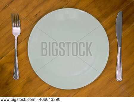 Empty Plate With Knife And Fork On Wooden Background. Cutlery And Plate On Wooden Backdrop. Photo Of