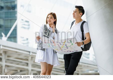 Portrait Of Young Asian Tourists Lover Couple Standing And Holding Paper Map Thinking Together Try T