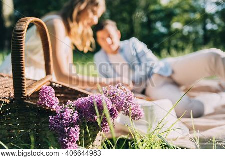 Lovely Couple In Love Organized A Picnic In The Park Wicker Basket With Flowers And Food On The Beds