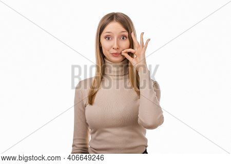 Your Secrets Safe With Me Concept. Blond Girl In Casual Clothes Showing Zip Gesture As If Shutting M