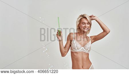 Sensual Young Woman In Sexy Lingerie Looking Aside, Having Fun While Blowing Soap Bubbles, Posing Is