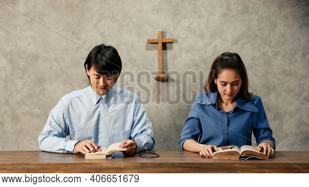 Asian Women And Men, The Faithful And Christian Are Reading The Bible To Pray To Jesus In The Crucif
