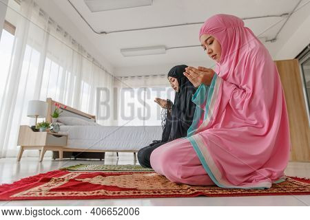 Asian Muslim Women Wear Black And Pink Hijab. Doing Supplications To Show Humility To God. In Faith