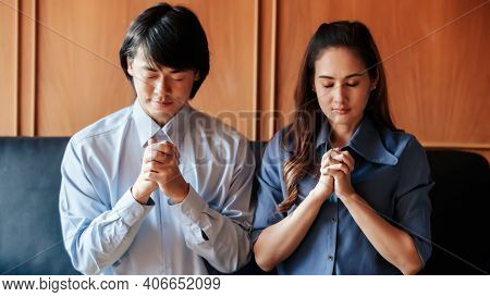 Asian Christian Woman And Man Holding Hands In Praying For Jesus' Blessings To Show Love And Confess