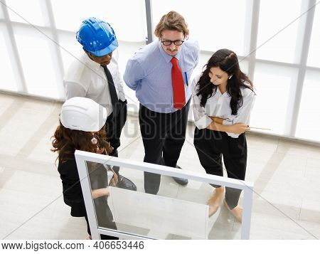 Image Is Topview. A Man Engineering African American And Caucasians As A Group Meeting On Constructi