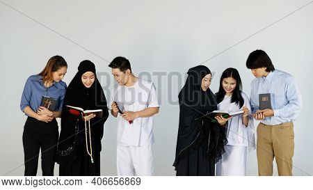 Asian Men And Women Of Different Religions Have Buddhism, Muslims, Christ. Bible Quran. A Smiling Fa