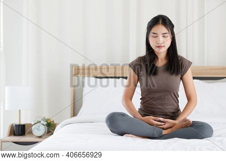 Female Buddhist Sitting On Bed In The Bedroom And Doing Meditation In Buddhism Religion Style. The I