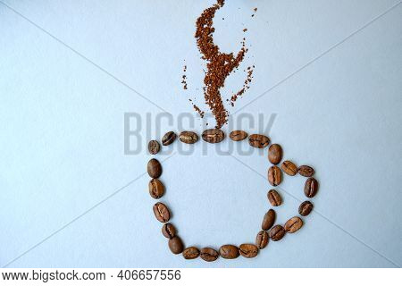 A Cup Of Coffee Made From Coffee Beans With Smoke On It. Coffee Consept. Cup On Gray Background.