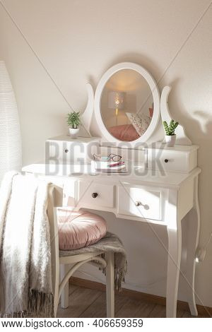 Detail of makeup dressing table with large mirror, diary and organizer. White and clean workstation in the master bedroom. Nobody inside.