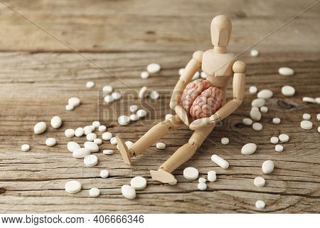 Toy Man Holds Brain In His Hands, Sits Next To Pills. Treatment Of Headache And Depression. Drug Ove