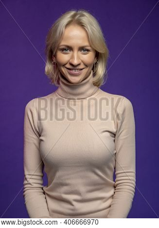Studio Portrait Of A Smiling Blonde Woman 25-30 Years Old On A Colored Background In A Light Sweater