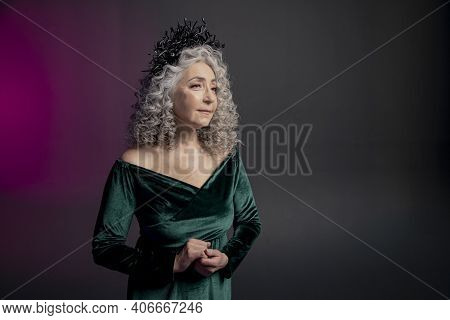 Studio Portrait Of An Elderly Woman 60-65 Years Old In A Beautiful Dress With A Crown On Her Head On