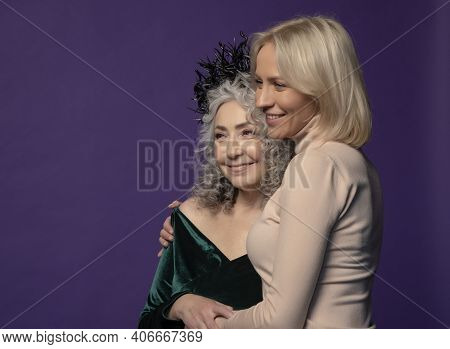 Studio Portrait Of An Elderly Woman 60-65 Years Old Embracing A Young Woman 25-30 Years Old On A Col