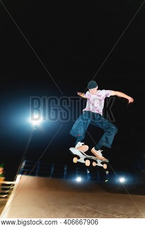 Young Guy Skateboarder Doing A Jump Trick At Night In A Skatepark