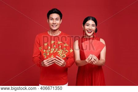 Happy Asian Couple In Red Casual Attire With Holding Angpao Or Red Packet Monetary Gift Of Congratul