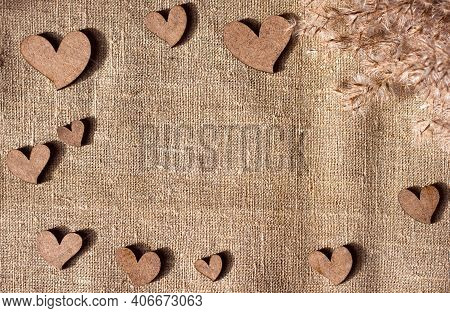 Decorative Wooden Hearts And Dried Reeds On Burlap Canvas Background, Love Theme And Valentine's Day