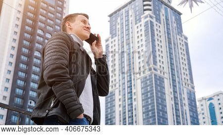 Confident Businessman Wearing Autumn Leather Jacket Speaks On Modern Smartphone Standings Against Hi