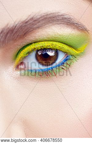 Make-up and cosmetics. Close-up portrait of a beautiful female eye with bright green and yellow make-up.
