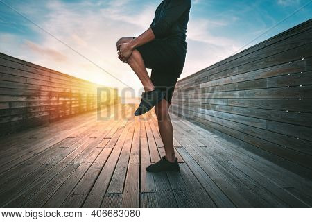 Sporty Man Warming Up And Stretching Legs Before Workout Outdoors At Sunset Or Sunrise. Stretching G