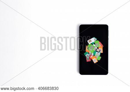 Heap Of Assorted Used Sim Cards For Cellular Communication On A Cell Phone On A White Background, Co
