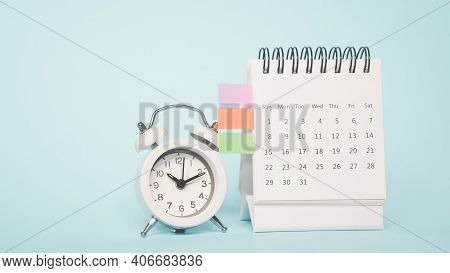 White Analog Alarm Clock On White Calendar With Grunge Blue Background With Copy Space, Business Mee