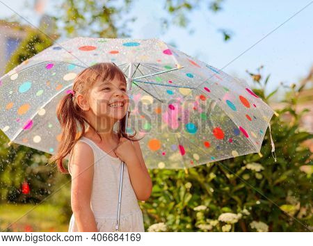 Happy Little Girl Plays In Garden Under The Summer Rain With An Umbrella.