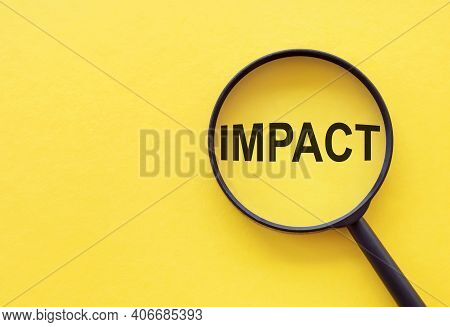 The Word Impact Is Written On A Magnifying Glass On A Yellow Background.