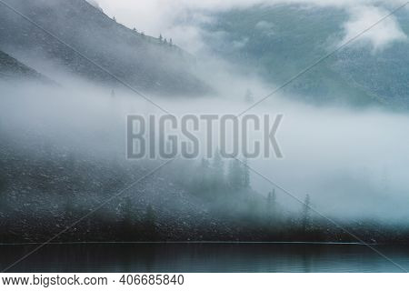 Dense Fog Above Tranquil Mountain Lake. Calm Water And Stony Steep Slope With Coniferous Trees Among