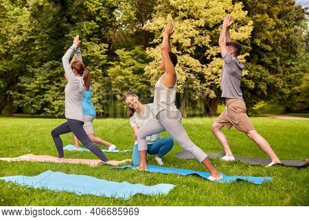 fitness, sport and healthy lifestyle concept - group of happy people doing yoga with instructor at summer park