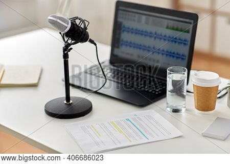 post production, podcast and technology concept - microphone and sound editor program on laptop computer at office