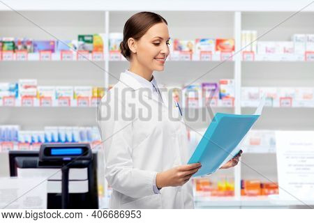 medicine, profession and healthcare concept - happy smiling female doctor in white coat with folder over pharmacy background