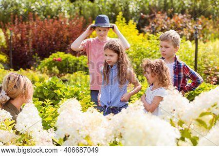 Children Listen The Teacher At The Flower Garden