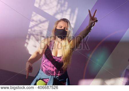 Young Blonde Girl Zumba Trainer Wears Black Mask During Pandemic