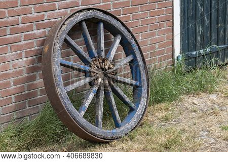 Old Incomplete Blue Wooden Cart Wheel Against A Brick Wall In The Netherlands