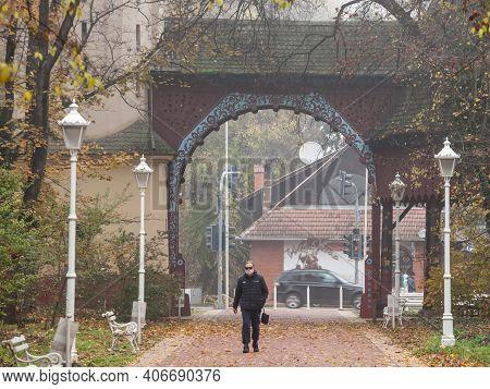 Palic, Serbia - November 18, 2020: Middle Aged Man Walking In The Aleja Of Palic, Near Subotica, Wea