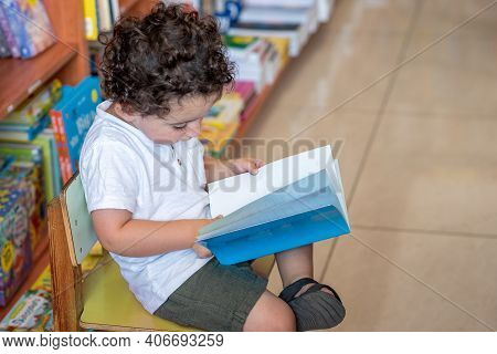 Little Boy Indoors In Front Of Books. Cute Young Toddler Sitting On A Chair Near Table And Reading B