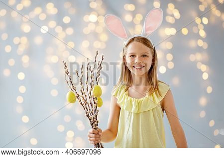 easter, holidays and people concept - happy smiling girl wearing bunny ears headband holding willow branches decorated with eggs over bokeh lighs