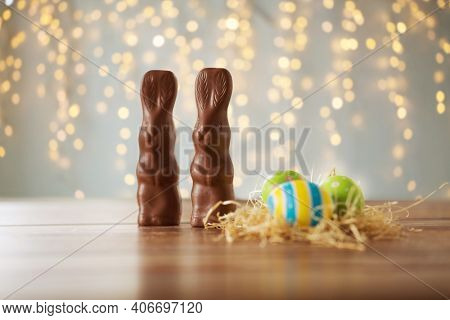 easter, holidays and object concept - close up of colored eggs in straw nest and chocolate bunnies on wooden table over bokeh lighs