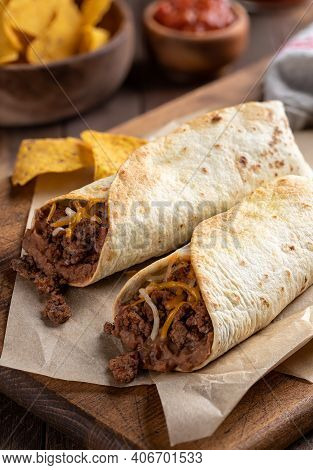 Burritos With Ground Beef, Refried Beans And Cheese On A Wooden Cutting Board