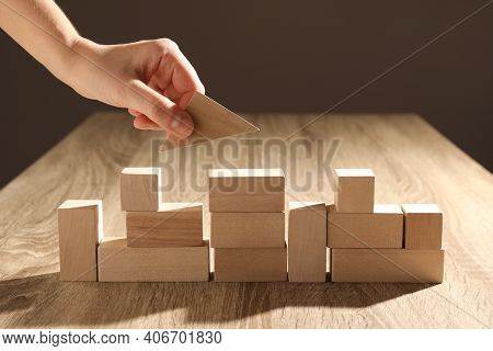 Woman Constructing With Wooden Building Blocks, Closeup. Corporate Social Responsibility Concept