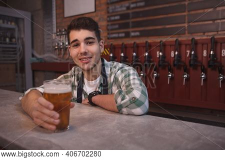 Young Bartender Smiling Joyfully, Serving Glass Ov Delicious Light Beer, Copy Space