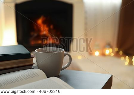 Cup Of Hot Drink And Books On Table Near Fireplace At Home. Cozy Atmosphere