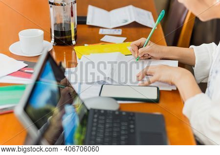 Woman Paying Bills Online And Writing Notes At Home.