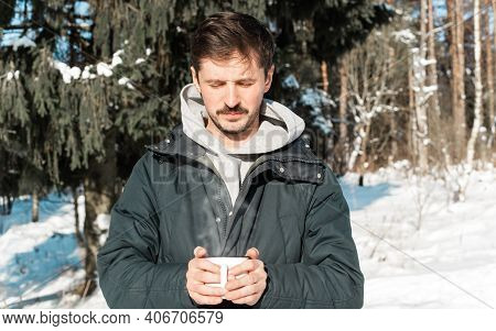 Young Man With Mustache Warming His Hands About Mug Of Hot Drink In Winter Outside. Camping In The W