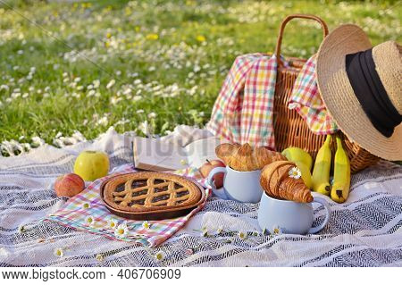 Picnic Basket With Fruit And Bakery On A Plaid And A Green Meadow With Flowers.lunch Sweet Cake, Cro